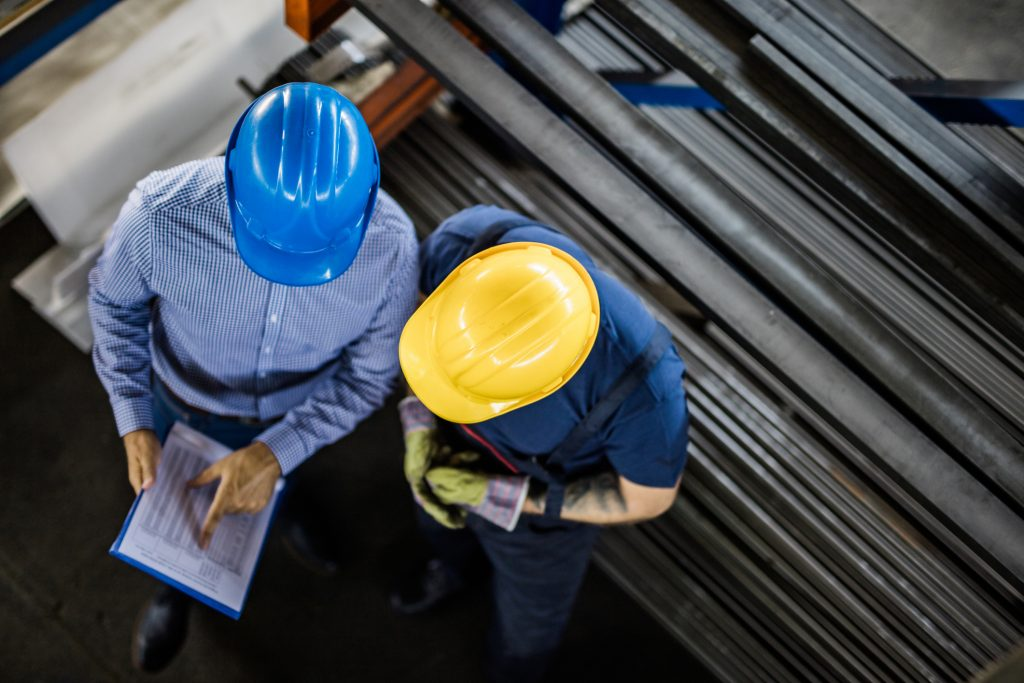 High angle view of an inspector and steel worker going through reports in aluminum mill.