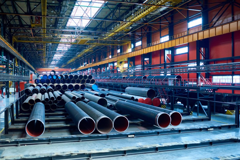 Abundance of tubes used for oil and gas industry placed in factory warehouse